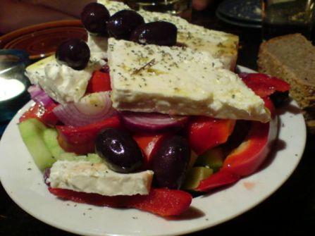 mit viel olivenoel versehener salat samt schafskaese