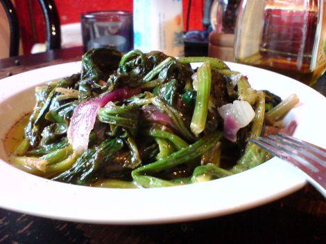 spinatblaetter mit roten zwiebelstuecken in olivenoel geduenstet und mit zitrone versehen
